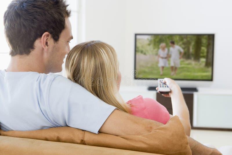 Paare in überwachendem Fernsehen des Wohnzimmers lizenzfreies stockbild