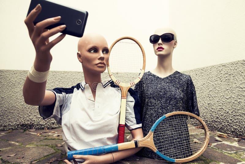 Paare Attrappen nehmen ein selfie, das in Siebziger gekleidet wird, die Tennis kleiden lizenzfreies stockbild