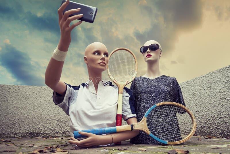 Paare Attrappen nehmen ein selfie, das in Siebziger gekleidet wird, die Tennis kleiden stockfoto