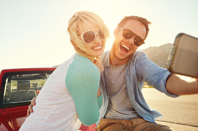 Paare auf Autoreise Sit On Convertible Car Taking Selfie lizenzfreie stockfotos
