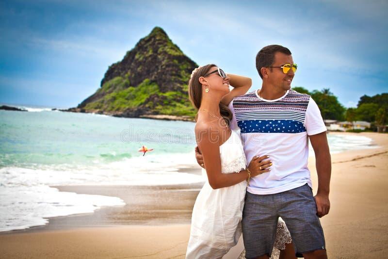 Paare auf dem lächelnden Halten des Strandes um einander stockfoto