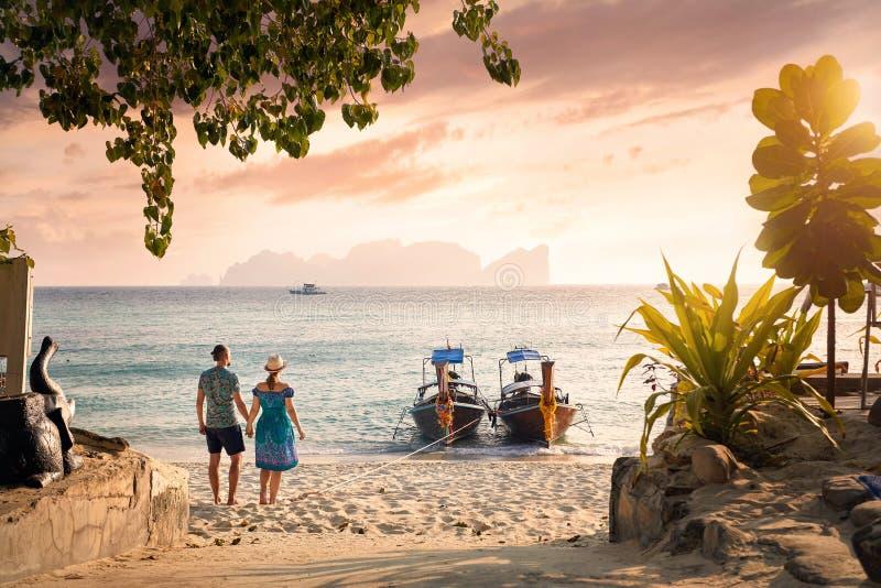 Paare auf dem tropischen Sonnenuntergangstrand lizenzfreie stockfotos