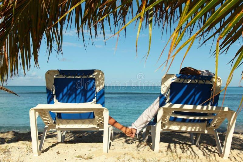 Paare auf den Sonnenaufenthaltsräumen, die Feiertage genießen lizenzfreie stockbilder