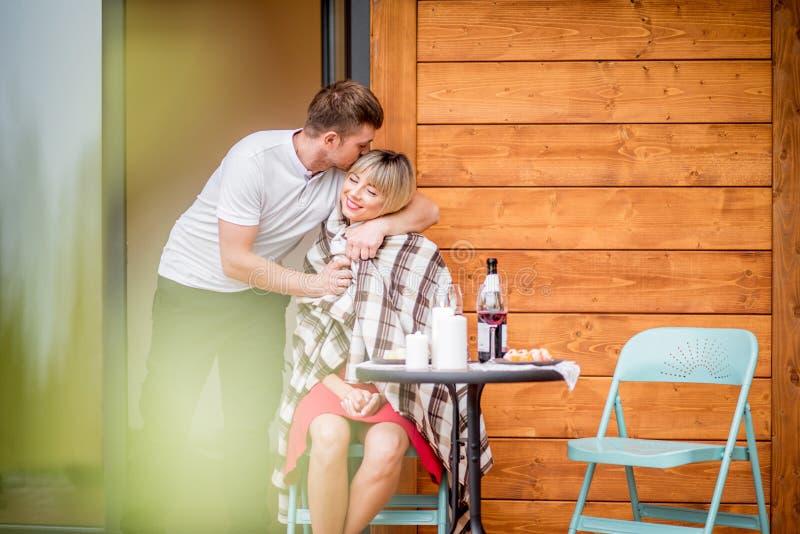 Paare auf der Terrasse des Holzhauses lizenzfreie stockfotos