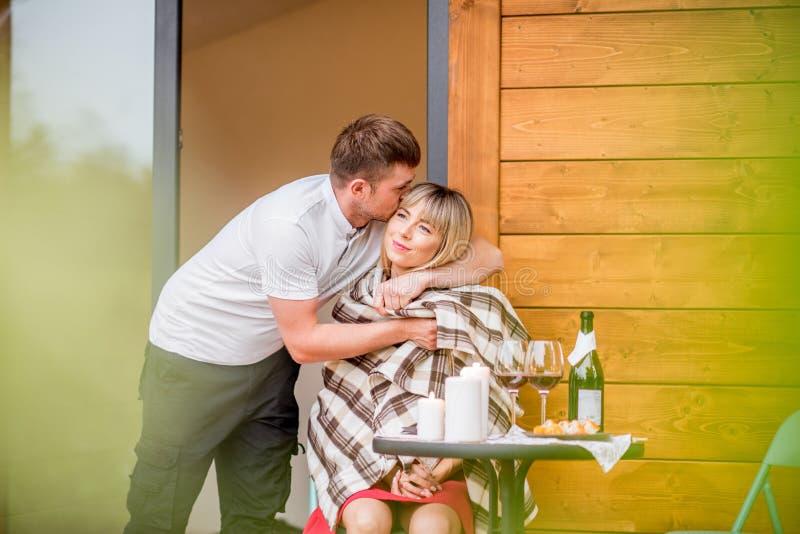 Paare auf der Terrasse des Holzhauses lizenzfreie stockbilder