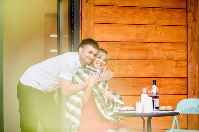 Paare auf der Terrasse des Holzhauses stockfotos