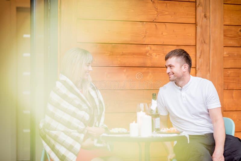 Paare auf der Terrasse des Holzhauses stockfotografie