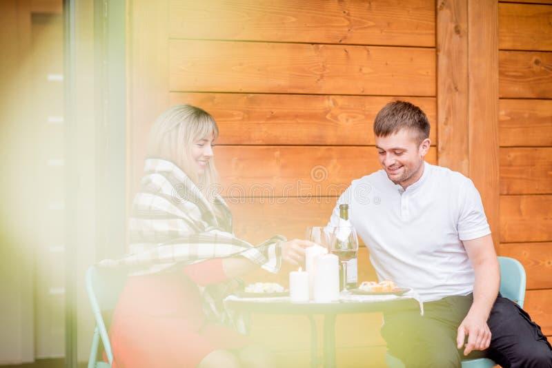 Paare auf der Terrasse des Holzhauses lizenzfreies stockfoto