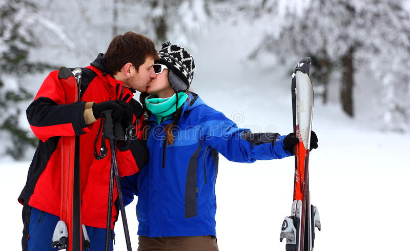 Paare auf einem Skifahrenfeiertagsküssen stockfotografie