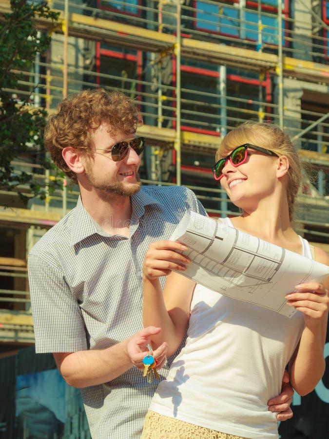 Paare auf Front des neuen Hauses mit Plan projektieren stockfoto