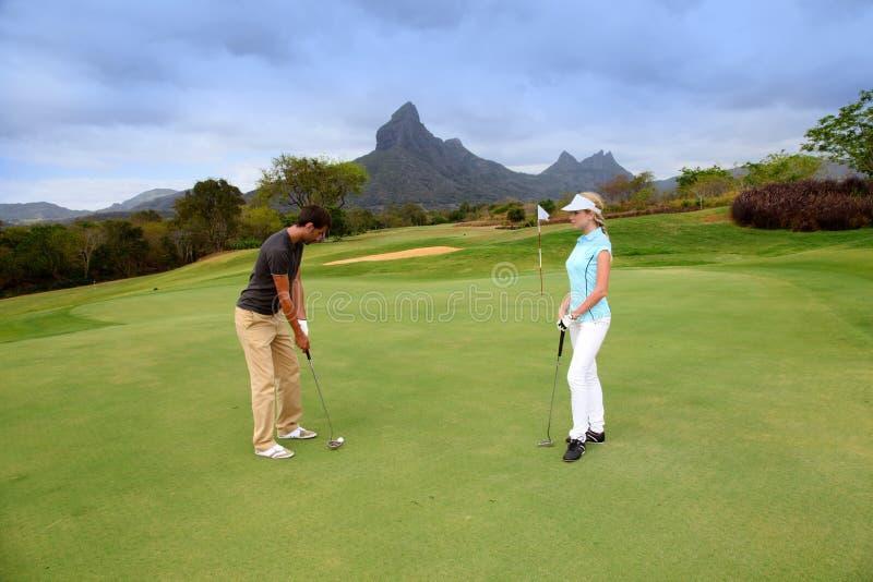 Paare auf Golfgrün lizenzfreie stockfotografie