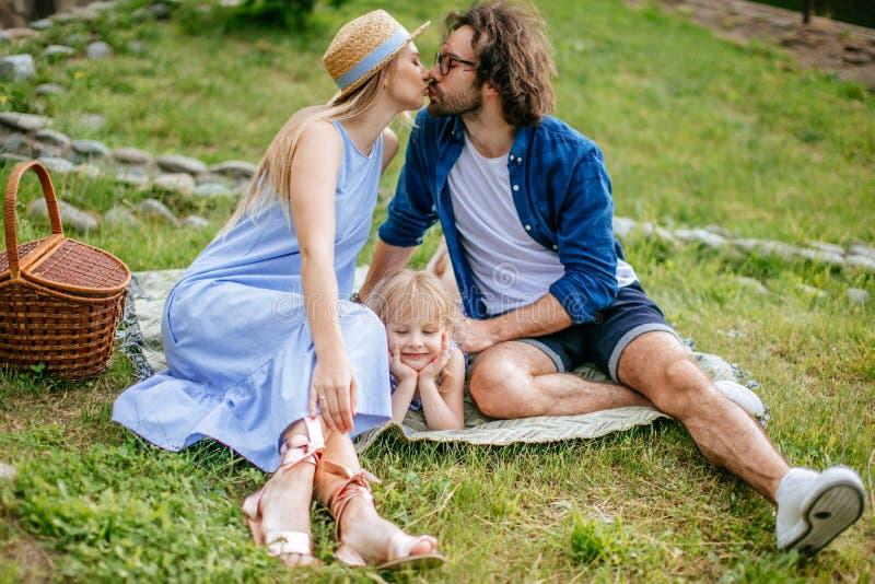 Paare auf Picknick auf dem Gebiet am sonnigen Sommertag genießend und stillstehend küssend und haben Sie Spaß lizenzfreies stockbild