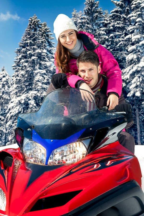 Paare auf Schneemobil fahrung lizenzfreies stockfoto