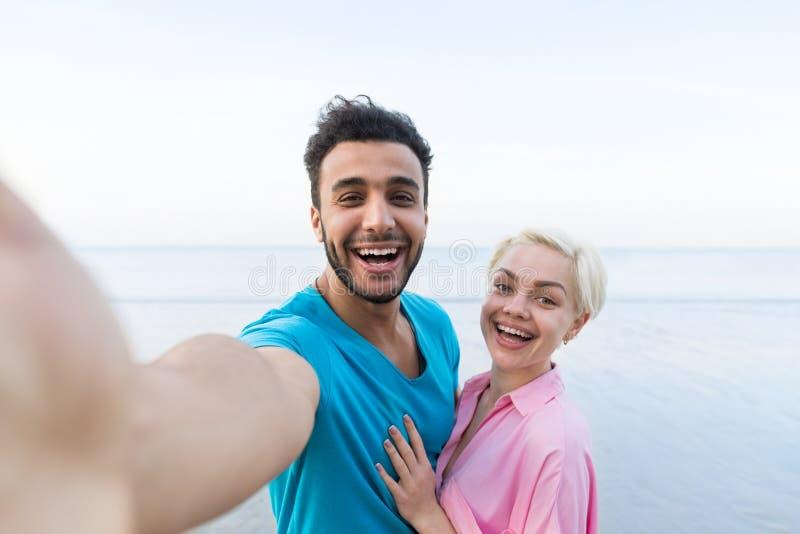 Paare auf Strand-Sommer-Ferien, schöne junge glückliche Menschen, die Selfie-Foto, Mann-Frauen-Umarmungs-Meer machen stockbild