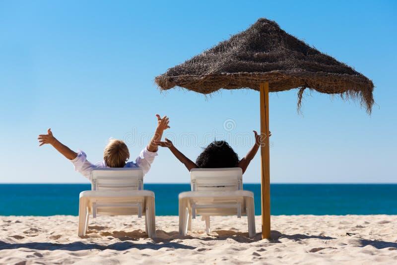 Paare auf Strand vacation mit Sonnenschutz stockfoto