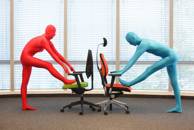 Paare in den elastischen Klagen des vollen Körpers, die mit Stühlen im Büro trainieren stockfotos