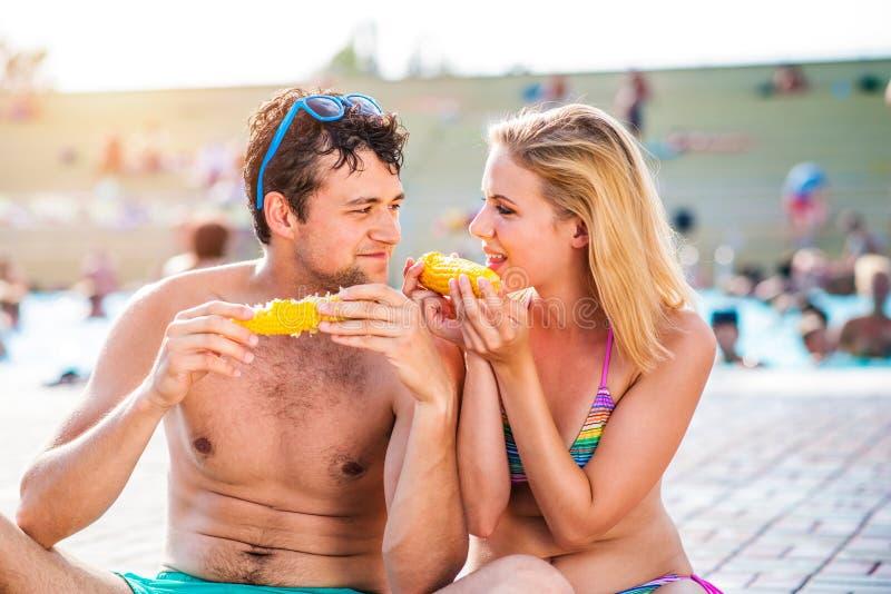 Paare in den Schwimmenklagen am Pool, das Mais isst lizenzfreies stockbild