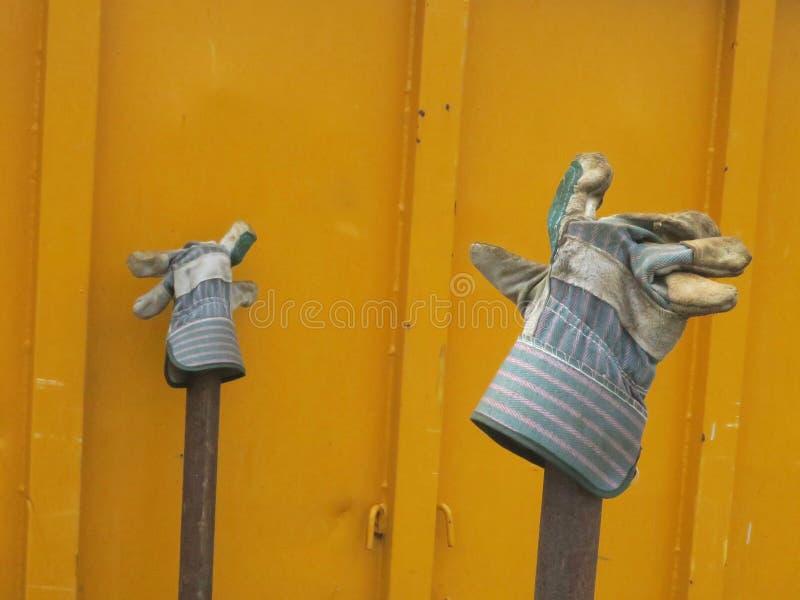 Paare der Arbeitshandschuhe auf Stangen nahe einem gelben Behälter stockfotografie