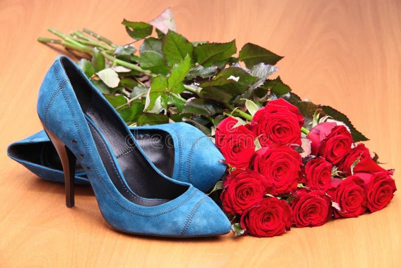 Paare der blauen weiblichen Schuhe und Bündel rote Rosen lizenzfreie stockfotos