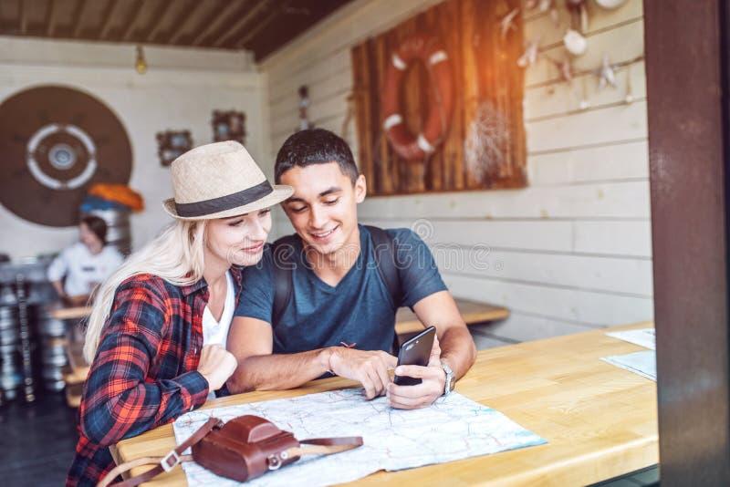 Paare in der Cafeteria unter Verwendung des Smartphone beim Reisen stockbild