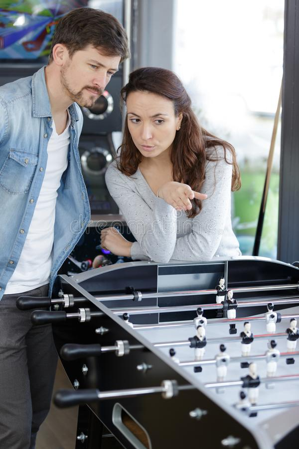 Paare in der Diskussion durch Tischfußballspiel lizenzfreie stockfotografie