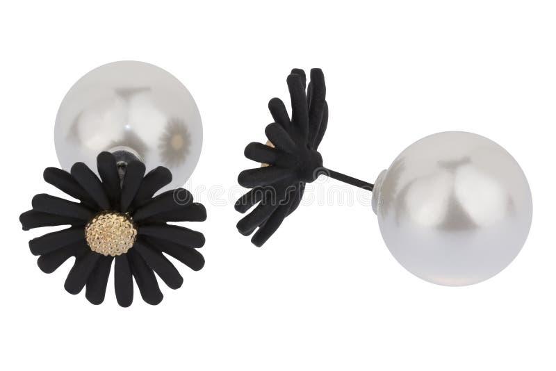 Paare der doppelten silbernen Ohrringe, wenn großer Perle und große schwarze die Blume, auf weißem Hintergrund lokalisiert sind,  stockfotografie