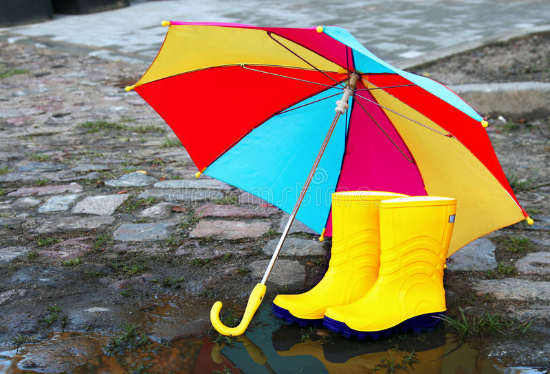 Paare der gelben Gummimatten mit einem geöffneten Regenschirm stockfotografie