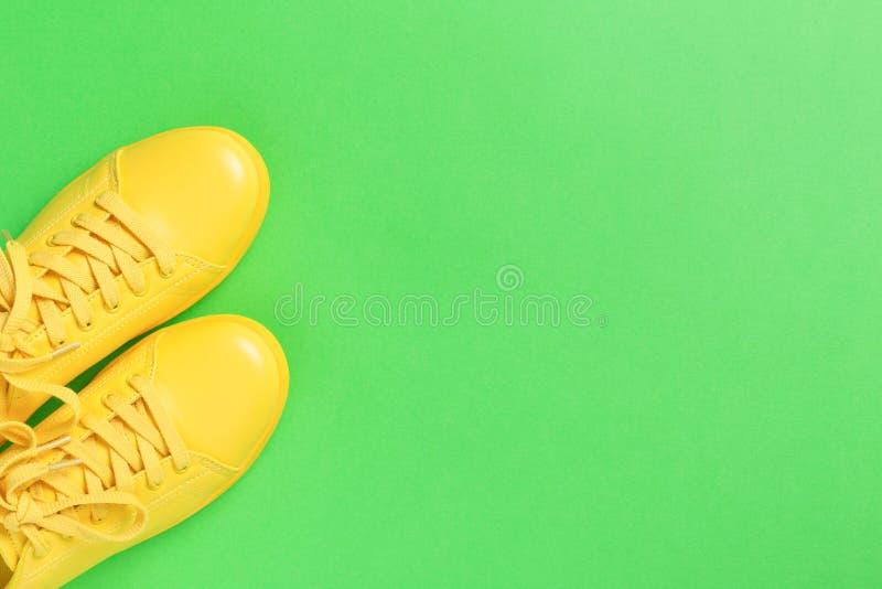 Paare der gelben Schuhe auf grünem Hintergrund stockbilder