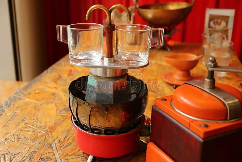 Paare der Glasdemitasseespressoschalen auf dem Herdplatteretro- Minikaffeebrauer mit Kaffeemühle im Vordergrund lizenzfreie stockfotos