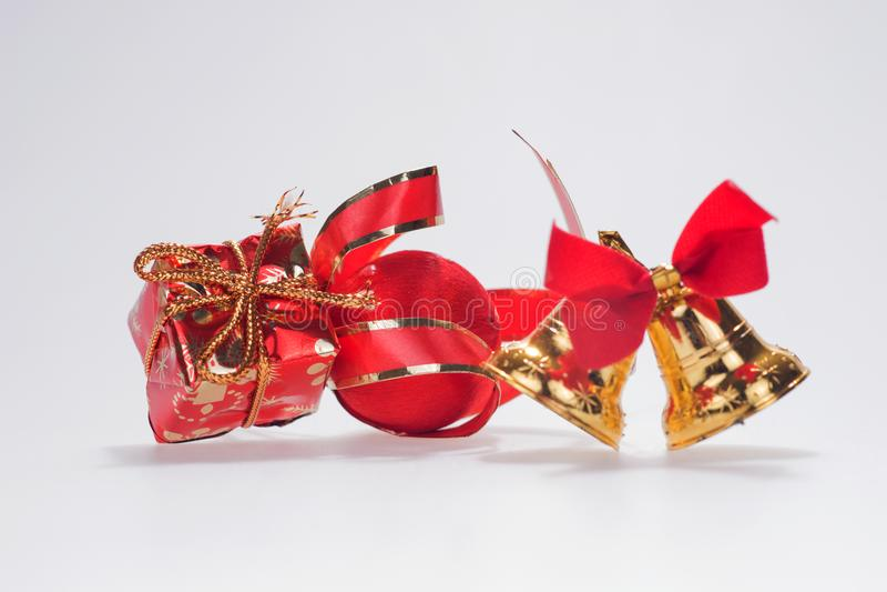 Paare der goldenen Glocken mit roter Weihnachtsgeschenkbox stockfotos