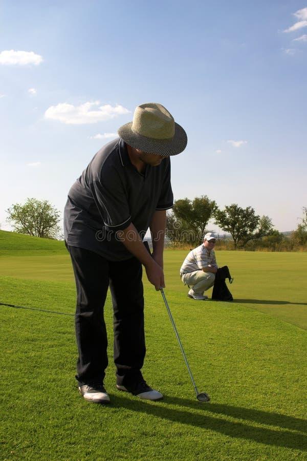 Paare der Golfspieler auf dem Grün. lizenzfreie stockbilder