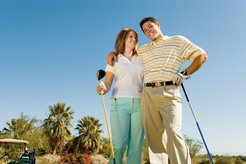 Paare der Golfspieler, die auf Golfplatz umfassen lizenzfreie stockfotos
