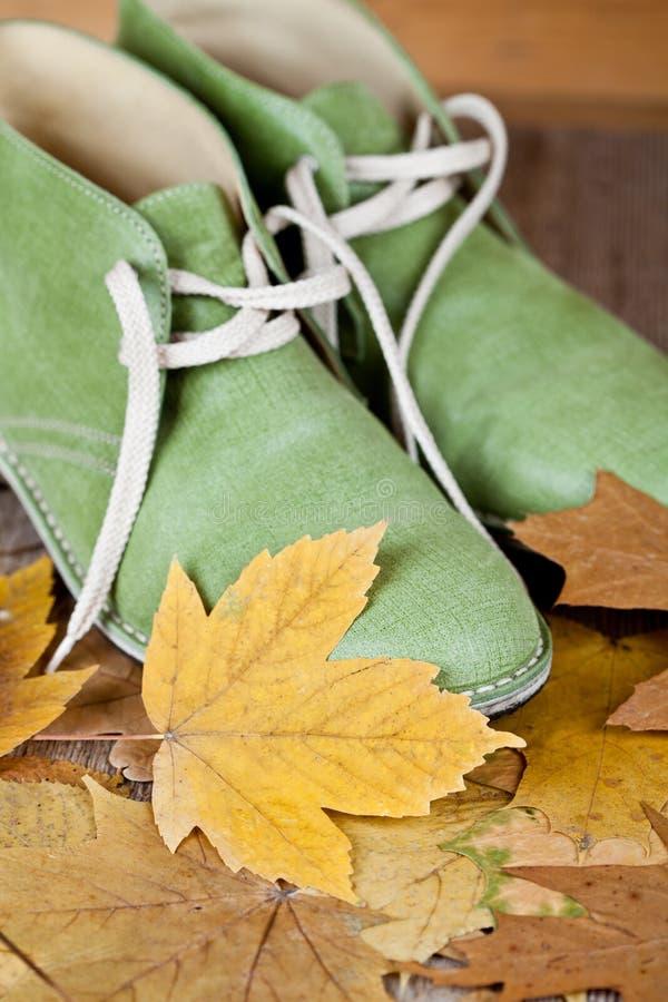 Paare der grünen Lederstiefel und der Gelbblätter lizenzfreie stockfotografie