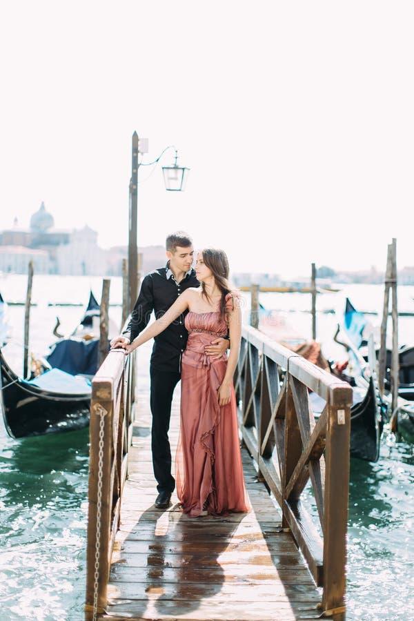 Paare der hübschen jungen Frau und des gut aussehenden Mannes stehen den Kanal mit Gondeln in Venedig, Italien bereit stockfoto