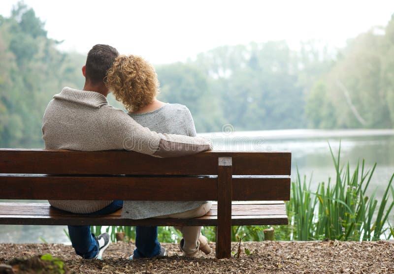 Paare der hinteren Ansicht, die draußen auf Bank sitzen stockfotografie