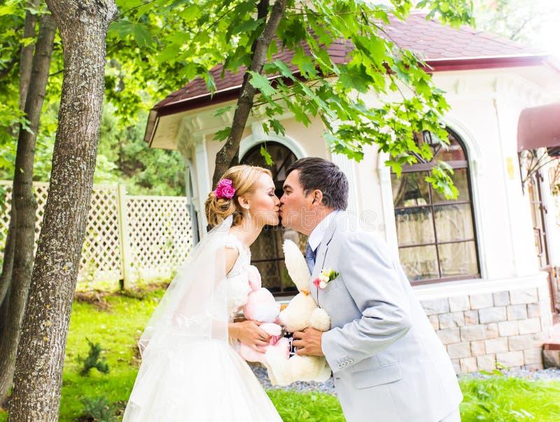 Paare in der Hochzeit bekleiden mit einem Blumenstrauß von Blumen und Grün ist in den Händen, in der Braut und im Bräutigamküssen stockfotografie