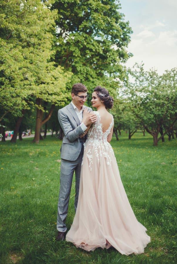 Paare in der Hochzeit bekleiden mit gegen dem Hintergrund des Parks lizenzfreies stockbild