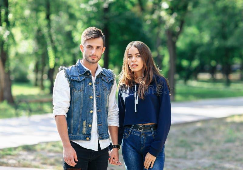 Paare der jungen Leute, die in den Park- und Griffhänden stehen stockfotos