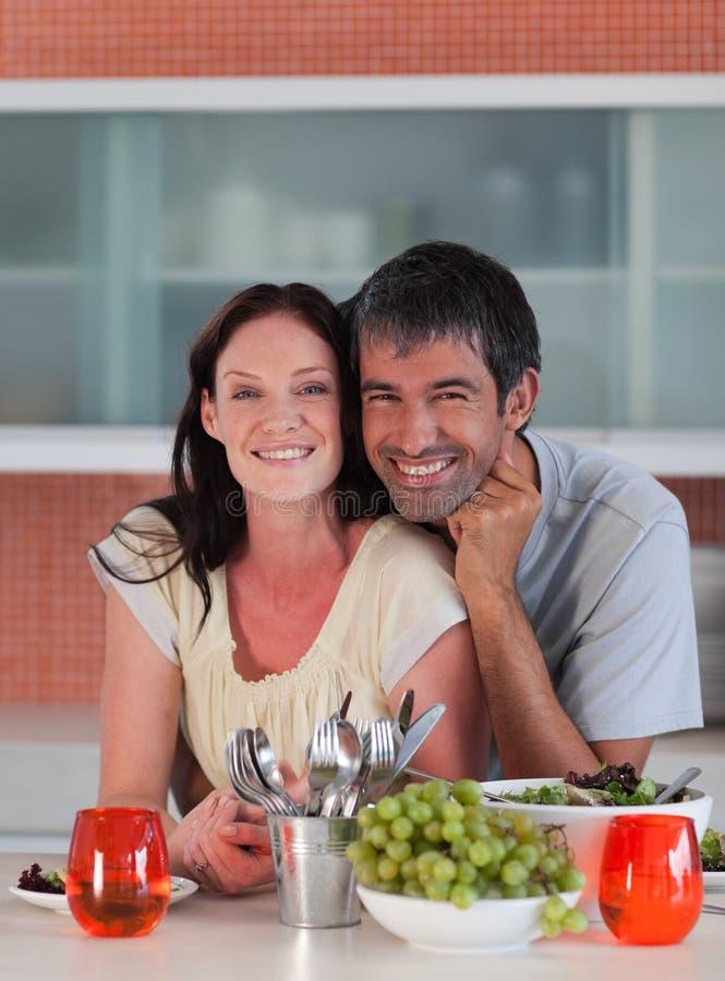 Paare in der Küche, die an der Kamera lächelt lizenzfreies stockbild