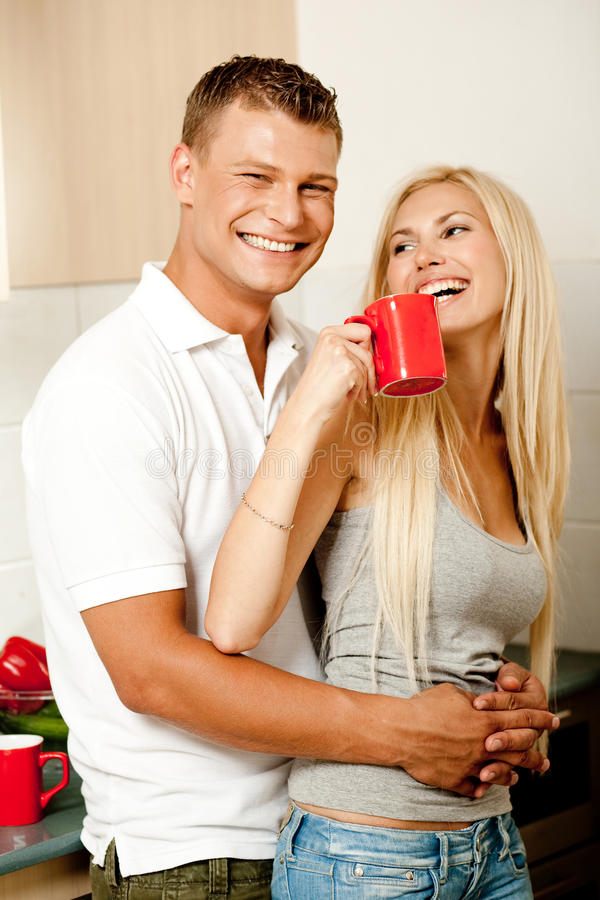 Paare in der Küche mit dem Kaffeelächeln lizenzfreies stockbild