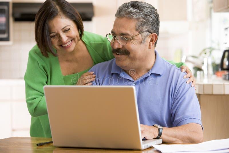 Paare in der Küche mit dem Laptoplächeln lizenzfreie stockfotos