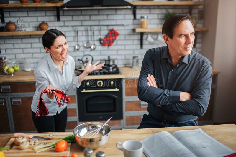 Paare in der Küche Theey haben zu argumentieren Kerl hört nicht auf Frau Sie versucht, mit ihm zu sprechen Sie sind umgekippt und stockfoto