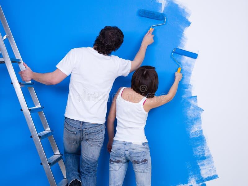 Paare der Leute, welche die Wand malen lizenzfreie stockfotografie