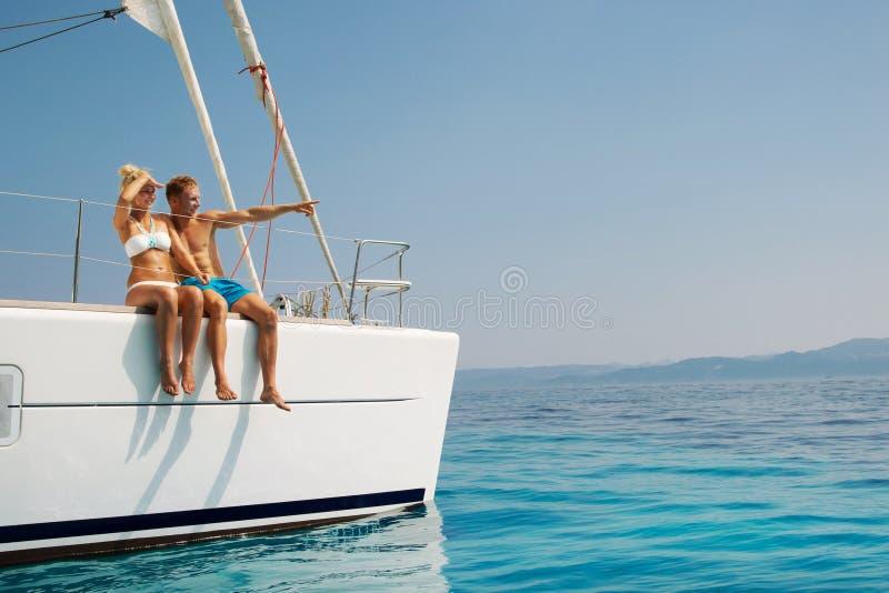 Paare in der Liebe auf einem Segelboot im Sommer lizenzfreie stockfotos