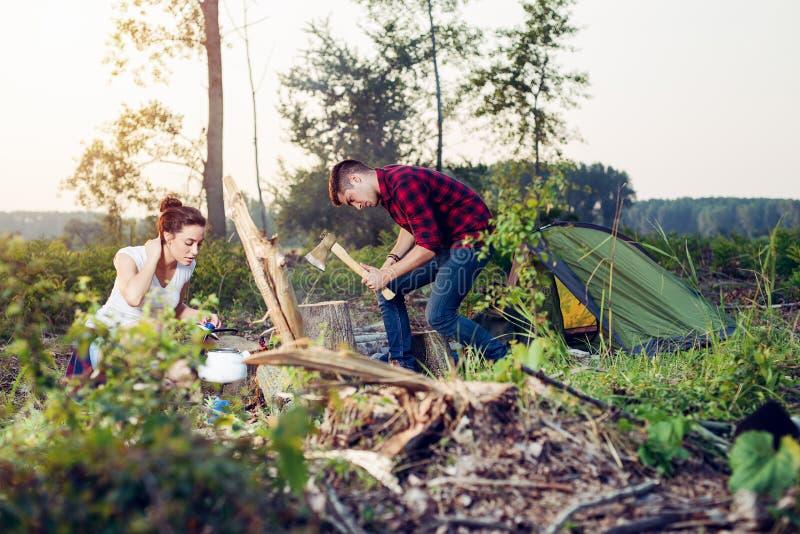 Paare in der Liebe bereiten Grillfeuer im Holz vor lizenzfreie stockbilder