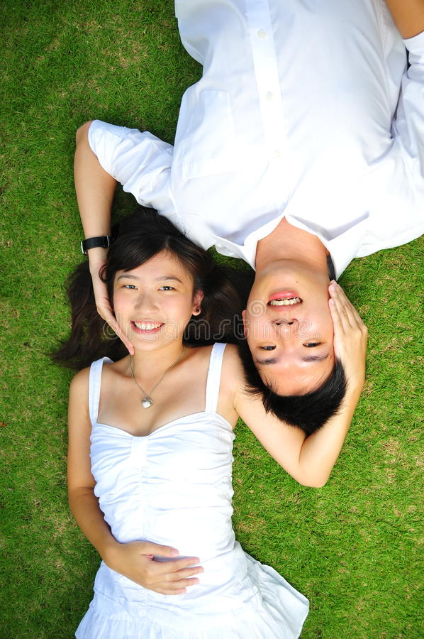 Paare in der Liebe, die auf dem Gras liegt lizenzfreies stockfoto