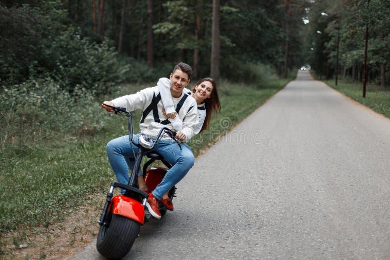 Paare in der Liebe, die ein elektrisches Fahrrad auf die Straße reitet lizenzfreies stockfoto