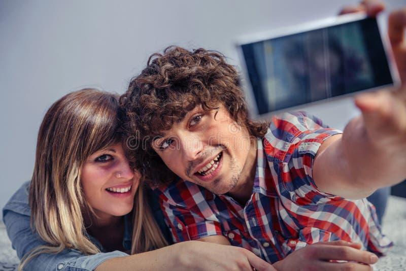 Paare in der Liebe, die selfie mit Smartphone auf Bett nimmt stockbilder