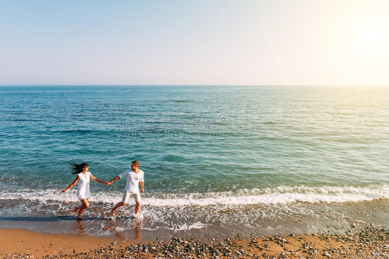 Paare in der Liebe, die Spa? auf dem Strand hat Flitterwochenreise Die Paare reisen Mann und Frau auf dem Strand Gl?ckliche Paare lizenzfreies stockbild