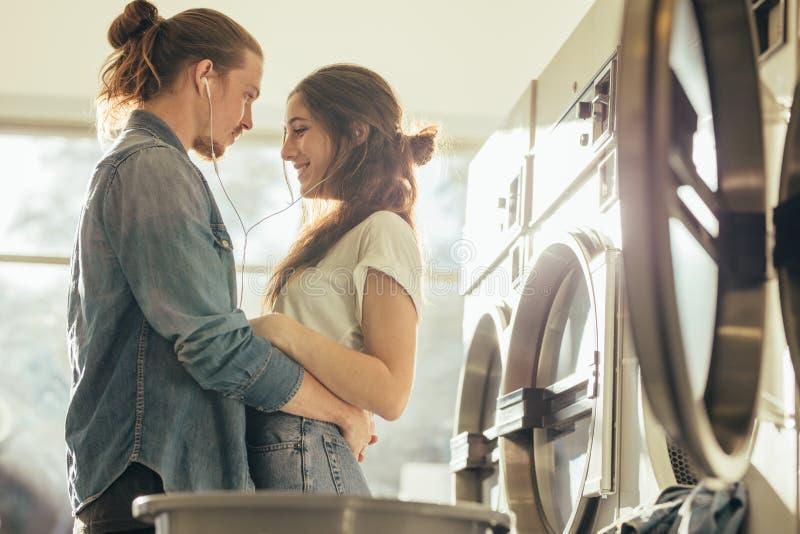 Paare in der Liebe, die zusammen steht, hörend Musik in Wäscherei r lizenzfreie stockbilder